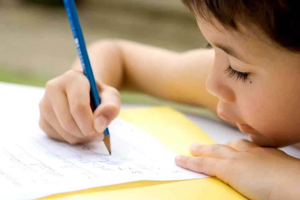 Chłopiec za biurkiem dla dziecka z regulowaną wysokością
