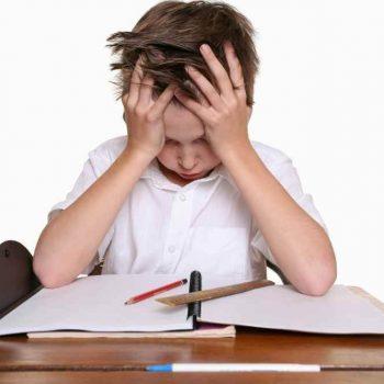 Chłopiec przy biurku z regulowaną wysokością