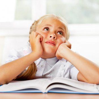 Dziewczynka za biurkiem z regulacją wysokości blatu